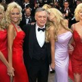 hugh-hefner-with-playmates-red-dresses